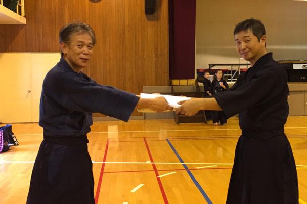 宇野先生(右)に袴を渡す真島先生(左)